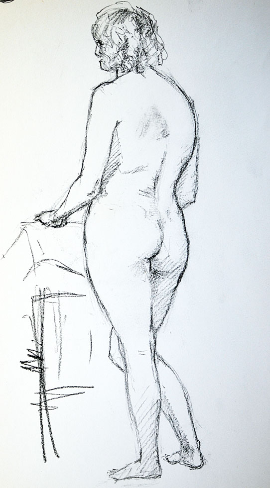 Female nude standing by chair